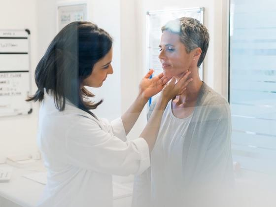 Doctor examining patient's thyroid.