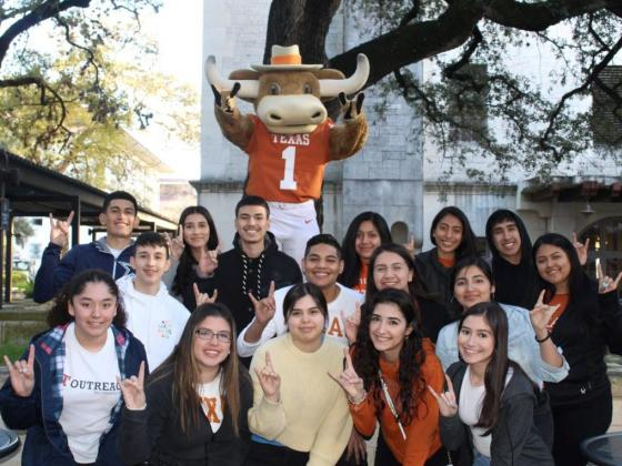 Students from the Youth Engagement Center hold up the hook 'em horns hand signal with Hook 'Em in the background
