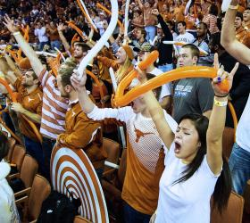 Longhorns fans cheering for the team in a packed stadium.