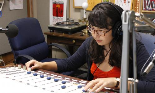 Student adjusting sound board in KVRX studio.