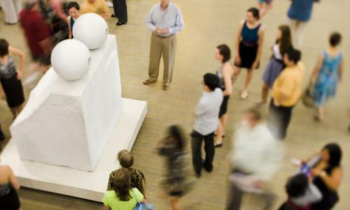 "Visitors surround Louise Bourgeois' sculpture ""Eyes."""
