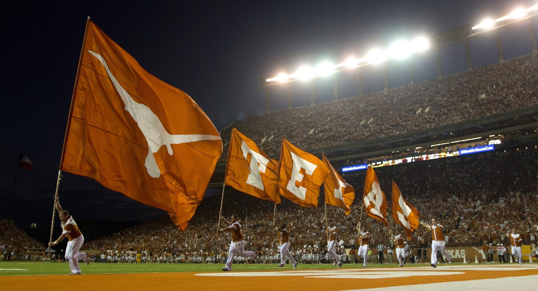 Texas cheerleaders running with flags through the endzone at a football game.