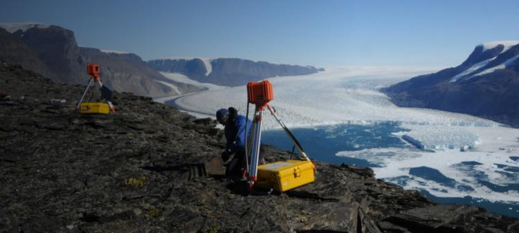 Leigh Stearns of the University of Kansas adjusts a time lapse camera monitoring a glacier in Greenland