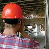 Architect wearing hard hat on construction site.