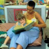 College student reading book with young child.
