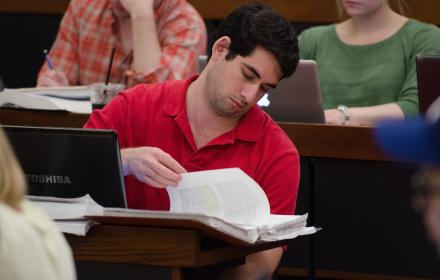 Law student looks through notes while in class.