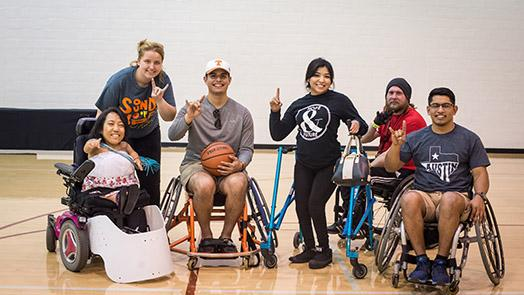 Students in wheelchairs hold up the hook 'em horn hand gesture on a basketball court