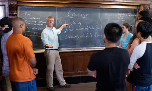Students in classroom in front of chalk board listening to faculty member.