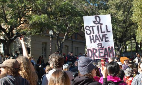 """Student holding sign saying """"I still have a dream"""" on MLK Day"""