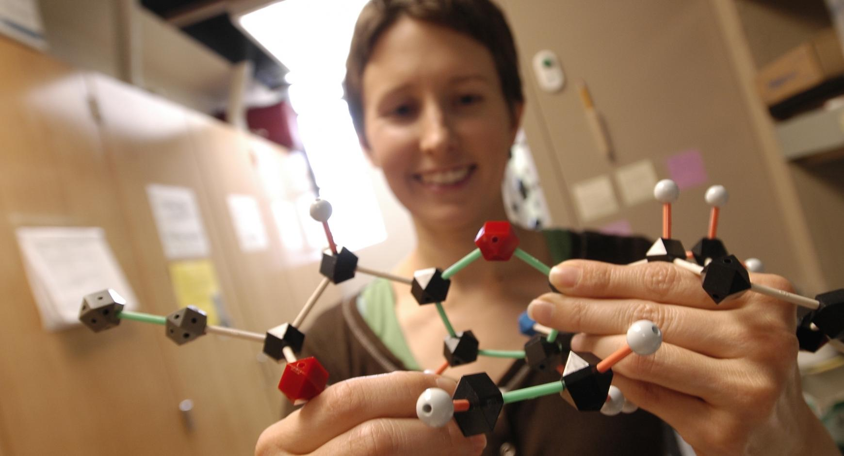 Student in lab holding a chemistry model.