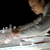 Student arranging model of city.