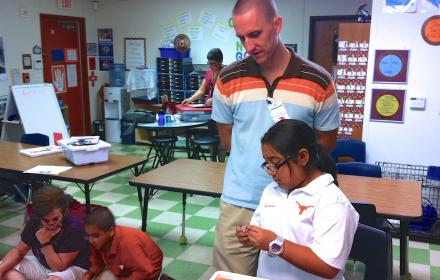 Teacher observing young student.