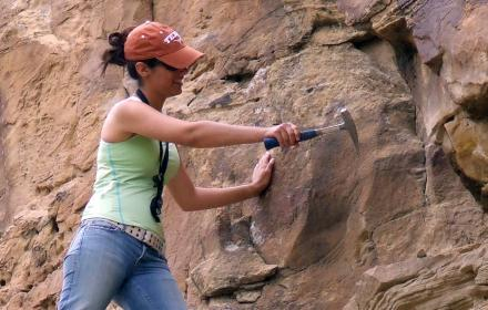 Student using rock hammer to gather samples while on field trip to Nine Mile Canyon.
