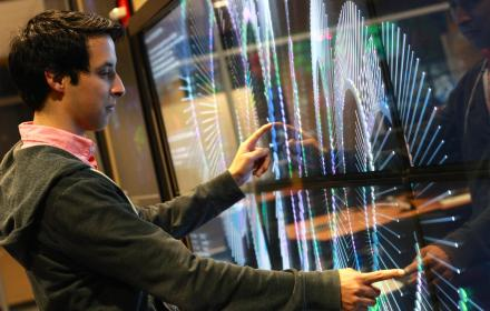 An undergraduate researcher using a large touchscreen in the TACC Vislab