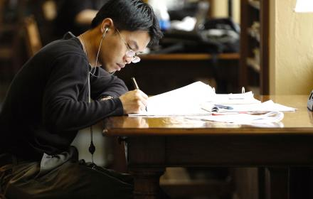 Student studying lecture notes in library.