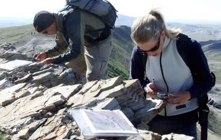 Students atop mountain on field trip examine rocks.