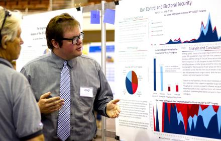 An undergraduate researcher presents his findings using a large-format poster at the Longhorn Research Bazaar